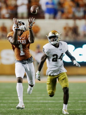 Texas wide receiver John Burt (1) catches a 72-yard touchdown pass in front of Notre Dame defensive back Nick Coleman during the second half Sunday. Texas won 50-47 in double overtime.