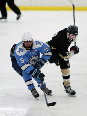 From left, Pelham's Ben Hurd (9) battles for puck control with Clarkstown's Kevin Stash  during hockey action at the Ice Hutch in Mount Vernon Dec. 23, 2016.