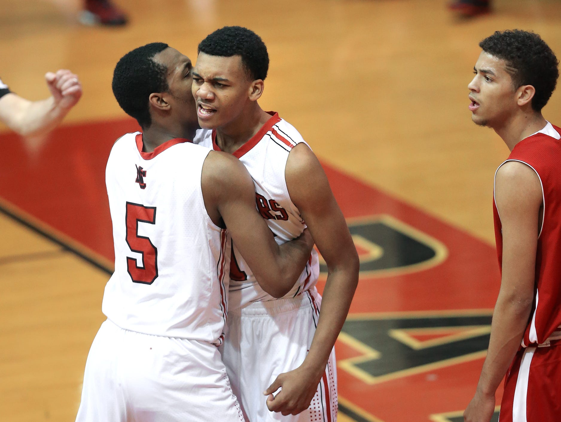 North Central's Antonio Singleton, right, celebrates a slam dunk with teammate Tyrie Johnson against East Chicago Central, Dec. 30, 2014.