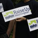 Supporters of raising the state minimum wage hold signs at a July 6 news conference in Olympia, Washington. Initiative 1433 seeks to incrementally increase the state's rate over the next four years to $13.50 an hour and to provide paid sick leave to employees who don't currently have it.