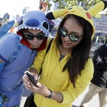 People costumed as the game's characters participate in a Pokemon Go search during a gathering of players Wednesday in San Francisco.