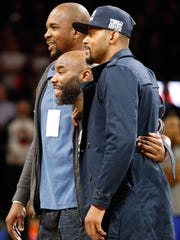 Former teammates for the Michigan State Spartans basketball team (near to far) Morris Peterson and Mateen Cleaves and Antonio Smith pose for a photo in support of the Flint water crisis relief effort before the game between the Detroit Pistons and the New York Knicks at The Palace of Auburn Hills. Pistons win 111-105.