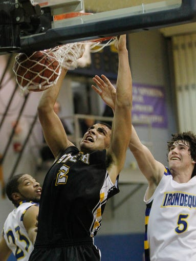 Athena's Anthony Lamb, center, puts home a dunk between Irondequoit's Antonio McIntyre, left, and Christian Shafer.