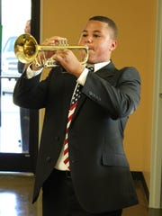 A young man plays taps during the ceremony.