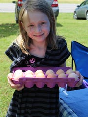 Sierra Grier shows off some of the eggs she gathers