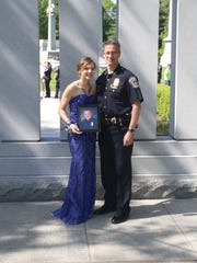 Before her prom, Sierra Bradway poses with IMPD Chief Bryan Roach with a photo of her father, Officer Rod Bradway, who was killed in the line of duty in 2013.