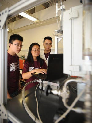 Civil engineering professor Pei Xu, center, works with graduate students Guanyu Ma, left, and Xuesong Xu in her laboratory.