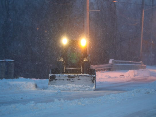 A small plow clears snow on Riverview Dr. by the Alan