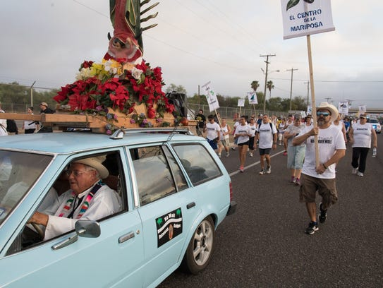 Father Roy Snipes leads a march to La Lomita chapel
