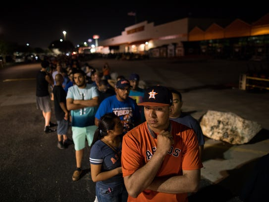 Fans wait inline outside Academy Sports and Outdoors