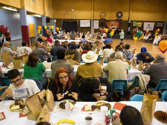 Families eat a Thanksgiving meal together during the
