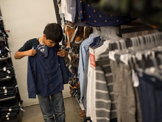 Nine-year-old Robert Contreras holds a shirt up to see if it would fit at Old Navy during a shopping spree for families with the Boys & Girls Clubs on Tuesday, Dec. 12, 2017.