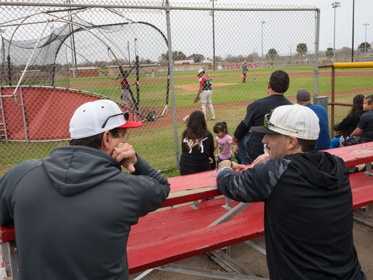 People sit in the stand a Ray High School as they watch