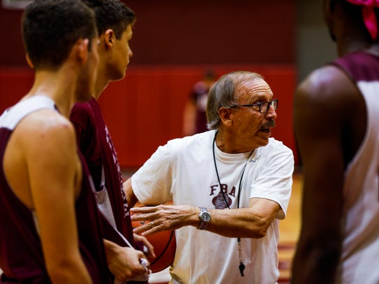 Don Stewart, the legendary former Lely High School coach now an assistant for his son Scott at First Baptist Academy, critiques a play during practice by the FBA boys basketball team on Monday.