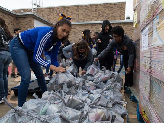 Students stack canned goods from the Coastal Bend Food