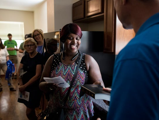 Dawn Marks accepts a Bible from Milwaukee Habitat for