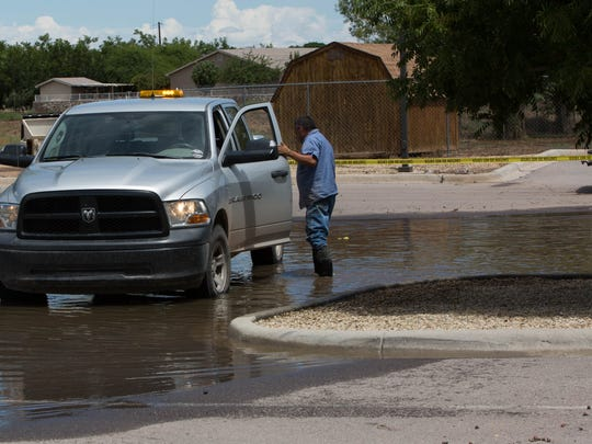 A Village of Hatch employee climbs into his truck outside the Hatch Valley Regional Public Safety building, where a water pump was at work removing water from the parking lot. Monday July 24, 2017.