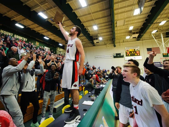 Rutland's Keegan Bliss (24) holds up the trophy to the fans during the Vermont state division I boys basketball championship game between the Mount Mansfield Cougars and the Rutland Raiders at Patrick Gym on Saturday afternoon March 17, 2018 in Burlington.
