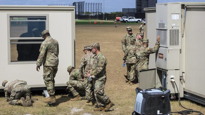 Florida Army National Guardsmen from the 50th Regional Support Group assist Palm Beach County as they begin setting up for drive-thru coronavirus testing at The Ballpark of the Palm Beaches in West Palm Beach Sunday morning, March 29, 2020. Testing will not be available Sunday.