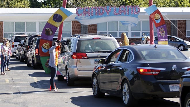 Edison Elementary third grade teacher Erika Heller waves to the vehicles as they enter the Candyland drive-thru celebration Monday to mark the end of the school year.