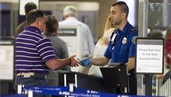 A TSA officer checks the credentials of a traveler