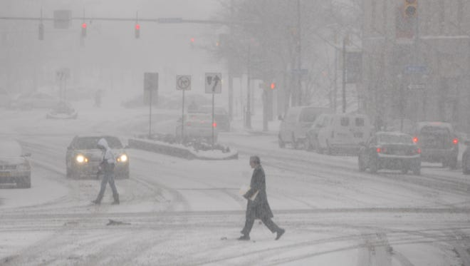 Pedestrians make their way through blowing lake effect snow in this Dec. 13, 2013 photo.