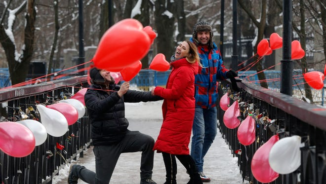 A man kneels in front of a girl on the Bridge of Love in Kiev, Ukraine, on Valentine's Day.