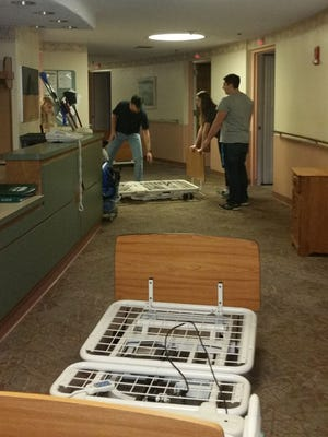 Volunteers from the American Foundation for Children with AIDS preparing to load dining room furniture, bedside tables and resident beds from Cornwall Manor's old Health Center. These items will be used in maternity wards and clinics in Kenya and Uganda.