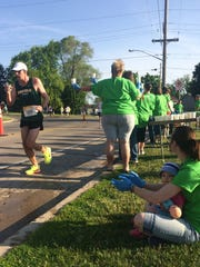 Jessica Hall, seated, and her 16-month-old daughter, Rooney, cheer as Kyle McMahon of De Pere runs past the mile 5 fluid station for the full marathon outside Christ The Rock Community Church in De Pere during the 17th annual Cellcom Green Bay Marathon on Sunday morning, May 22, 2016.