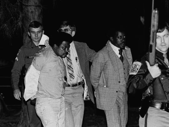 Police take members of the Taylor family into custody after a confrontation with plainclothes officers on Todd Road in Montgomery in 1983.