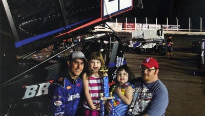Justin Henderson poses with Alexis Vanbochove (second from right) after presenting her with a trophy he won at a Huset's Speedway race this summer. Alexis died Wednesday from a rare form of brain cancer.