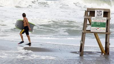 An Atlanta woman pulled from the ocean on Sunday after getting caught in a rip current, remains unresponsive, authorities reported.