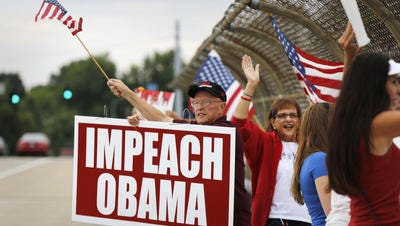 Tom Smith of Covington holds an Impeach Obama sign on Kyles Lane at the overpass.
