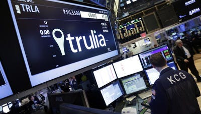 A specialist woks at the post that handles Trulia on the floor of the New York Stock Exchange Monday. Zillow is buying Trulia for $3.5 billion.