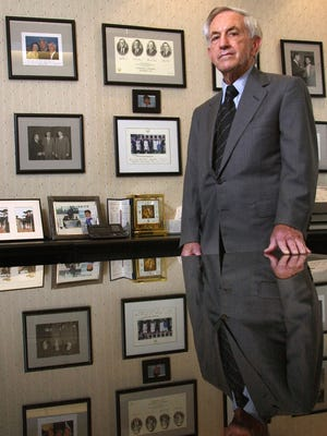 Bernard Waterman, owner of Waterman Broadcasting, stands in May 2002 with his collection of photographs of himself with politicians and celebrities, including John F. Kennedy, Jack Dempsey, and the Bush family.