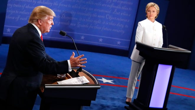 Donald Trump speaks as Hillary Clinton looks on during the final presidential debate.