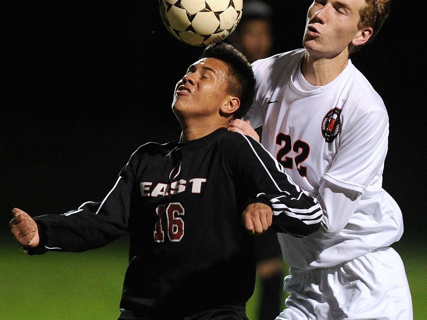Green Bay East's Manuel Villagrana heads a ball while defended by West De Pere's Calvin Perry in the first half of Tuesday's FRCC soccer game.