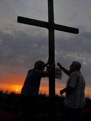 Timothy Beyer of Cocoa Beach and Pastor Kendall Nickell of Satellite Beach take down the cross after Sunday mornings Easter Sunrise Service held at Pelican Beach Park in Satellite Beach held by Our Father's House and Satellite Beach United Methodist Church .