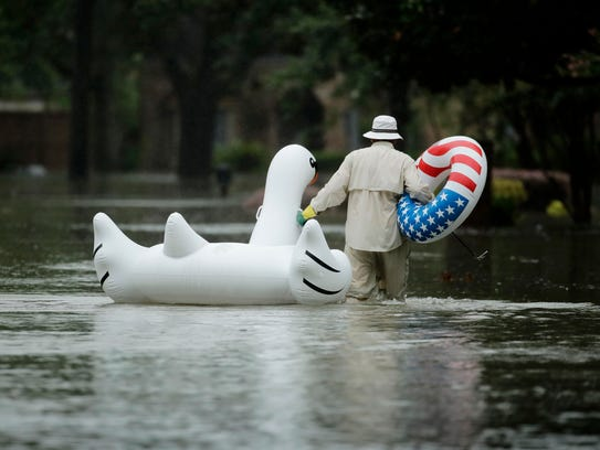 A man walks to his home in a neighborhood inundated