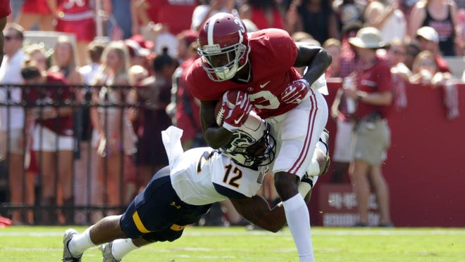 Alabama Crimson Tide wide receiver Calvin Ridley tries to avoid the tackle attempt by Kent State Golden Flashes defensive back Erik Simpson.