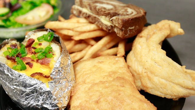 Beer-battered North Atlantic cod is plated with a baked potato, french fries and rye bread at Bryan's IDK Wings in the town of Maine.