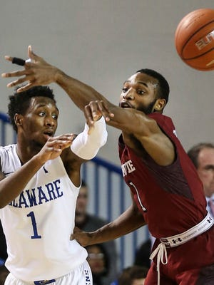 In this Dec. 18, 2014, file photo, Temple's Josh Brown, right, tries to block the pass of Delaware's Kory Holden during the first half of an NCAA college basketball game in Newark, Del. Holden knows many will write off South Carolina because of all the talent the Gamecocks lost from its Final Four team. He says that would be a mistake. The former high-scoring Delaware guard is expected to play a big role this season.