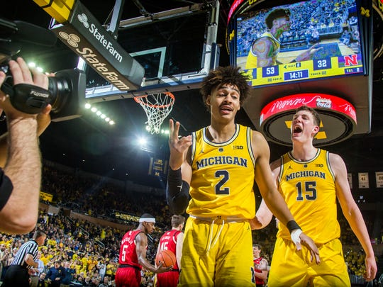 Michigan guard Jordan Poole (2) celebrates a slam dunk with center Jon Teske (15), in the second half of an NCAA college basketball game against Nebraska at Crisler Center in Ann Arbor, Mich., Thursday, Feb. 28, 2019. Michigan won 82-53. (AP Photo/Tony Ding)