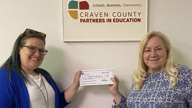 As the producer and director extraordinaire of the #VirtualPIELuncheon, Kim Scott earned her school, Oaks Road Academy, where she is the assistant principal, $300 for their general fund. The #VirtualPIELuncheon can be viewed on PIE's website at  https://cravenpartners.com/. Pictured is Kim receiving the check for her school from PIE executive director Darlene Brown.