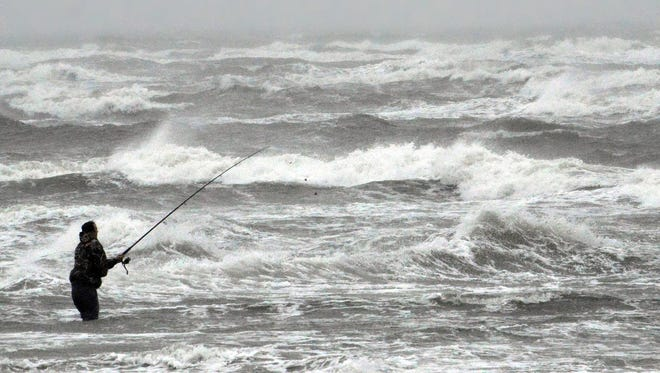 A fisherman in the surf.
