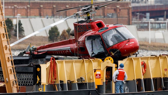 A crew member on a crane barge looks at the sightseeing helicopter that crashed on Sunday night after it was removed from the East River in New York on March 12, 2018.  Five people died in the accident, though the pilot survived, and investigators from the National Transportation Safety Board are on the scene.