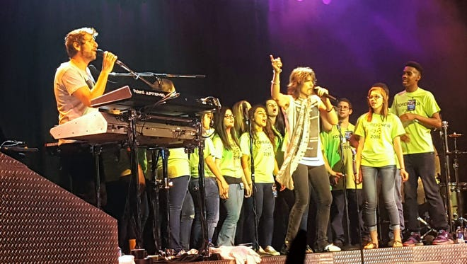 """Students in a Marksville High theater class sing the chorus of """"I Want to Know What Love Is"""" with Foreigner on stage Saturday at Paragon Casino and Resort."""