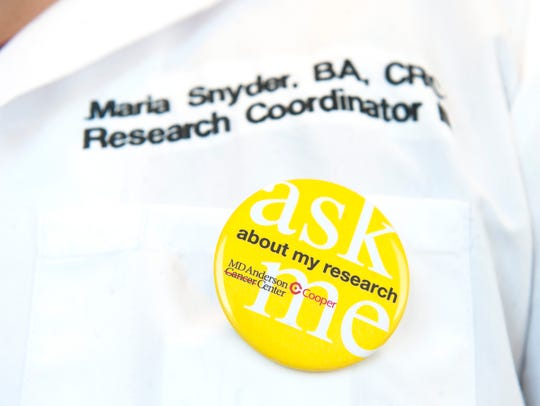 Research coordinator Maria Snyder wears a button designed to encourage patients to ask about the research at MD Anderson Cancer Center at Cooper in Camden, and to see if they qualify for clinical trials.