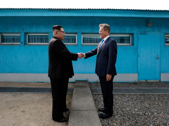 North Korea's leader Kim Jong Un shakes hands with South Korea's President Moon Jae-in at the Military Demarcation Line that divides their countries ahead of their summit at the truce village of Panmunjom on April 27, 2018.