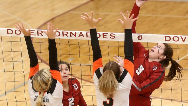 Dover's Tori Jones spikes the ball towards Ridgewood's Paige Slusser and Madisyn Colvin in a high school volleyball match at Dover Monday night, It was the first official match in the new Tornadoes gymnasium.